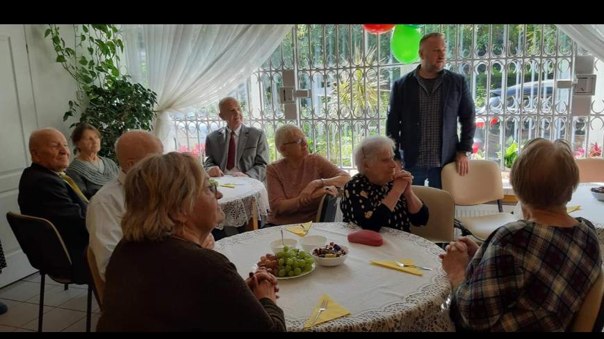 Seniorzy siedzący przy dwóch okrągłych stołach